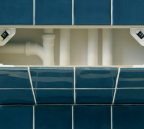 Open blue tiled access panel showing plastic pipework behind