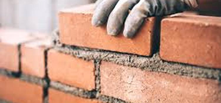 Man wearing safety gloves laying a course of brickwork