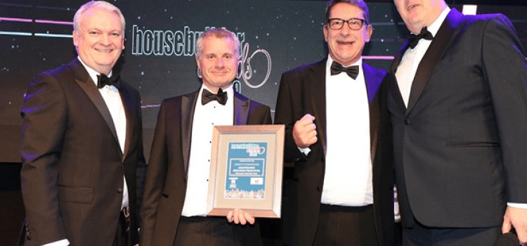 Gareth Wright, Sales Director and Mike Challinor, R&D Director on stage being presented with award by Dara O'Brien at black tie event